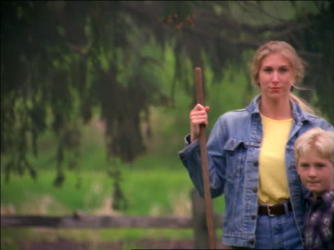 vídeos de stock, filmes e b-roll de pan portrait blonde woman with rake standing with arms around son outdoors - jaqueta jeans