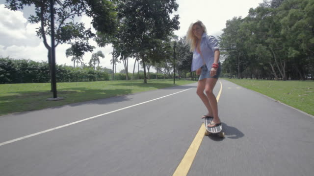 WS POV Blonde young woman skateboarding on road / Singapore, Singapore, Singapore