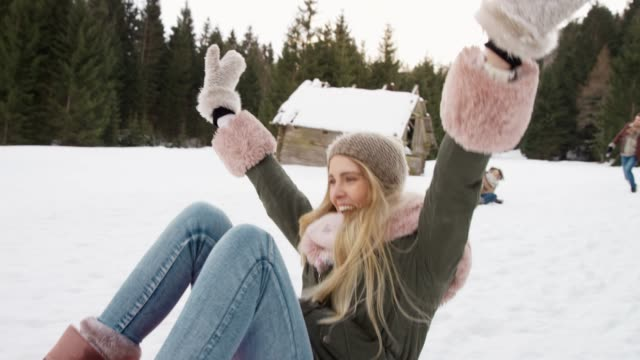 slo mo blonde young woman sliding down the hill in a snow sledge and laughing - sledge stock videos & royalty-free footage