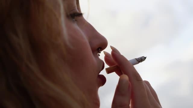 vídeos de stock e filmes b-roll de blonde young woman smoking cigarette and relaxing - cigarro