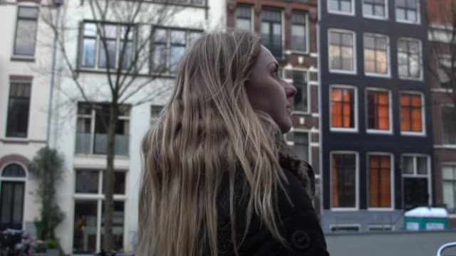 blonde young woman walking in amsterdam, netherlands - looking away stock videos & royalty-free footage