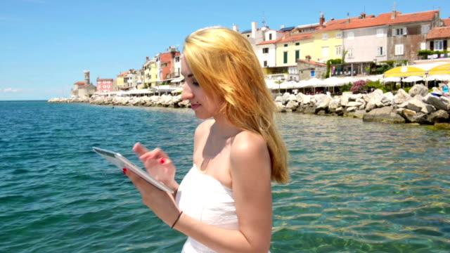 vidéos et rushes de blondy contre bleu de la mer avec une tablette - robe blanche
