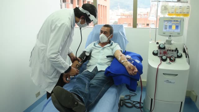 blood bank doctor santiago grass takes blood pressure to a man, who recovered from covid-19, and donates plasma on august 14, 2020 in bogota,... - blutplasma stock-videos und b-roll-filmmaterial