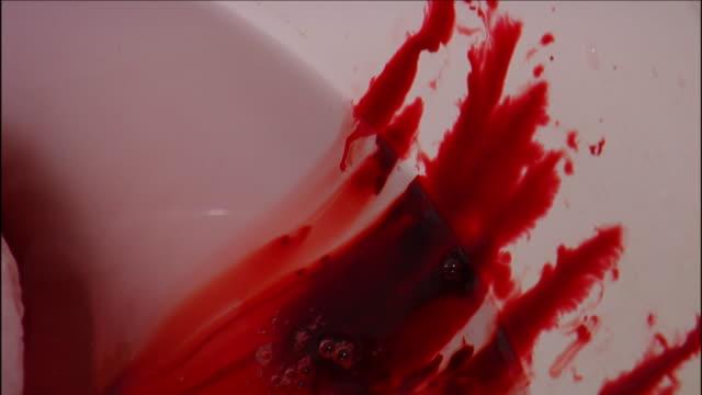 vidéos et rushes de blood clots cling to a toilet bowl as blood spills down the sides. - sang