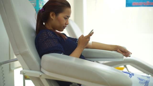 vídeos de stock, filmes e b-roll de doação de sangue e o uso de smartphone - veia humana