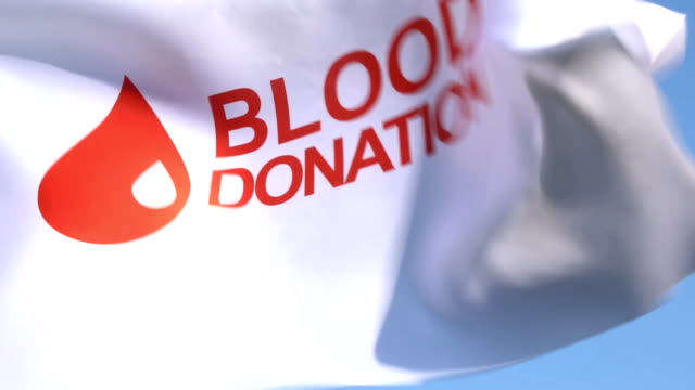 blood donation flag waving in sky - blood donation stock videos & royalty-free footage