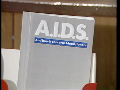 blood donor centres in uk under examination following haemophiliac deaths from aids; england: edgware: int man walks to reception desk at donor... - aids stock-videos und b-roll-filmmaterial