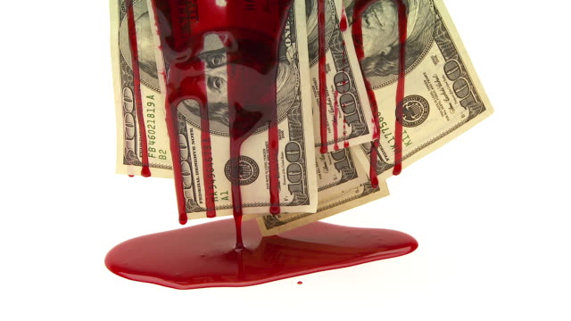 Blood dripping down a group of one hundred dollar bills, creating puddle