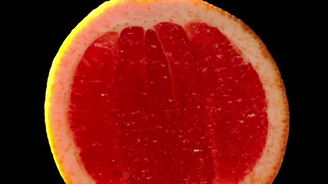 Blood grapefruit slowly rotating with black background