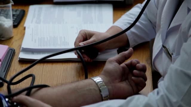vídeos de stock, filmes e b-roll de o teste de pressão arterial - braço humano