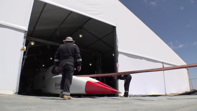 bloodhound half race car and half spaceship being brought out of workshop and into kalahari desert south africa ready for speed trials - test drive stock videos & royalty-free footage