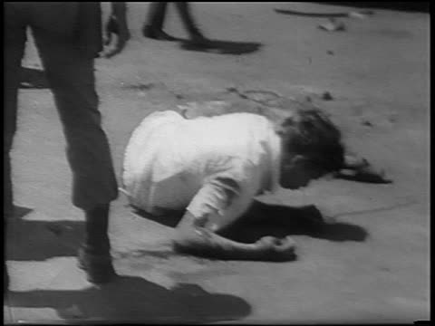 b/w 1967 bloody man lying on street in antichinese riot / jakarta indonesia / newsreel - violence stock videos & royalty-free footage