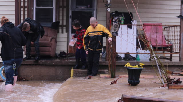 A family watches from their front porch as floodwaters surround their home on Spring Street in Bloomington Indiana after a flash flood