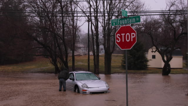 A good samaritan pulls a stalled car and its driver from flash flood waters at Fountain Drive and West 8th Street near the intersection of Fountain...