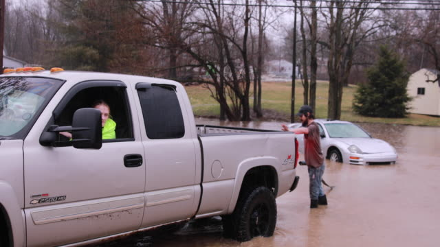 a good samiratan hooks a car to his truck at fountain drive and west 8th street near the intersection of fountain drive and adams flooding the... - tow truck driver stock videos and b-roll footage