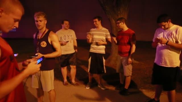 bloomington, indiana, usa: a group play pokémon go on their mobile phones at night near the art museum on the campus of indiana university. pokémon... - pokémon stock videos & royalty-free footage