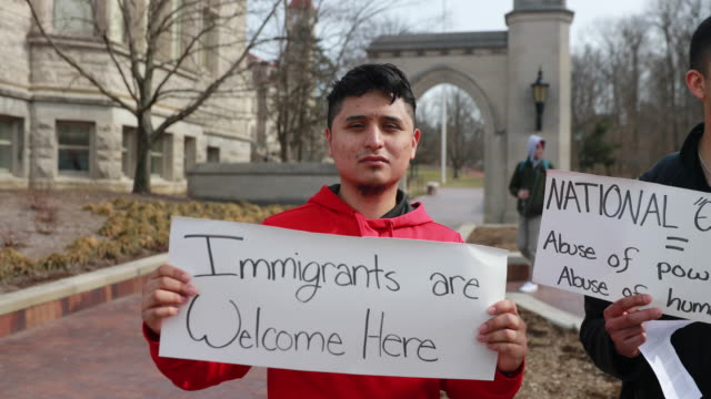 A protester holds a sign reading Immigrants are Welcome Here during an emergency protest against the fake national emergency at the Sample Gates on...