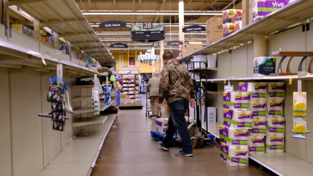 a worker restocks paper products including paper towels at kroger in bloomington just before the store is shutting down for the night at midnight... - regal stock-videos und b-roll-filmmaterial