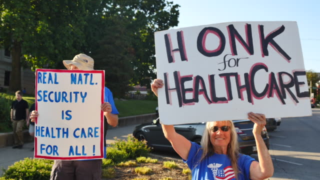 vídeos y material grabado en eventos de stock de activists show signs to passing motorists at monroe county courthouse during the medicare for all march and rally in support of universal healthcare... - medicare