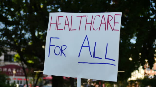 vídeos y material grabado en eventos de stock de an activist standing at the monroe county courthouse holds a sign reading health for all during the medicare for all march and rally in support of... - medicare
