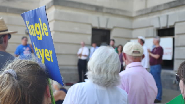 "vídeos y material grabado en eventos de stock de bloomington, indiana, usa: an activist standing at the monroe county courthouse holds a sign reading, ""single payer,"" during the medicare for all... - medicare"