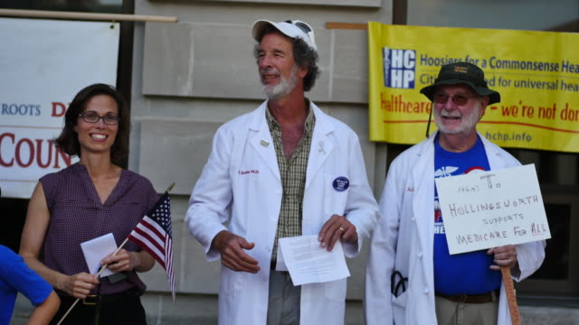 bloomington, indiana, usa: bloomington medical doctor rob stone, center, in favor of single payer universal healthcare, waits for marchers to arrive... - medicaid stock videos & royalty-free footage