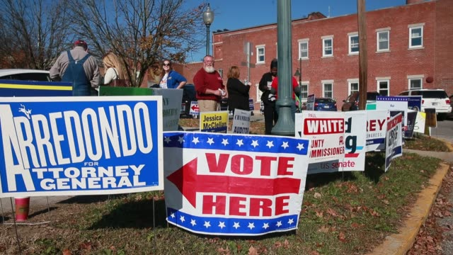 bloomington, indiana, usa: campaign signs fill a grassy area 50 feet from a line of voters on the last day of early voting at monroe county indiana's... - last day stock videos & royalty-free footage