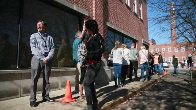 vidéos et rushes de bloomington, indiana, usa: election official jack davis, left, stands next to a cone at the end of a line of early voters lined up on the last day of... - file attente