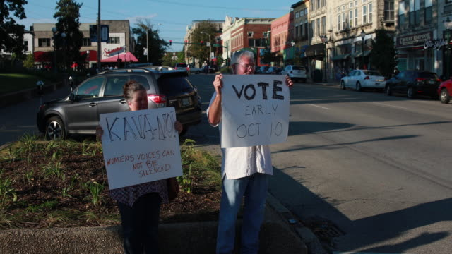 vidéos et rushes de bloomington, indiana, usa: laura zimmerman, left, and richard denning hold a spontaneous protest against the confirmation of brett kavanaugh as... - nomination