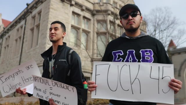 Protesters hold signs during an emergency protest against the fake national emergency at the Sample Gates on the Campus of Indiana University United...