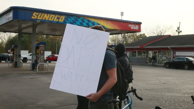 protesters hold signs in front of the sunoco gas station on south walnut street during a rally in solidarity with native american groups protesting... - south dakota stock-videos und b-roll-filmmaterial