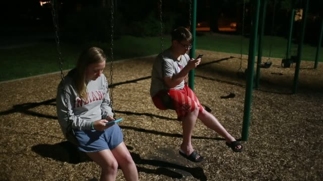 bloomington, indiana, usa: shelbie loonan-hesser, left, and kent ketter sit on swings and play pokémon go on their mobile phones at night in the... - pokémon stock videos & royalty-free footage