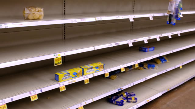 vídeos de stock, filmes e b-roll de shelves are cleared of pasta and other staples at a kroger in bloomington just before the store is shutting down for the night at midnight friday... - prateleira mobília