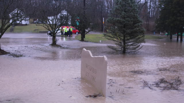 Waters flow past the Waterman neighborhood sign at Fountain Drive and West 8th Street near the intersection of Fountain Drive and Adams flooding the...