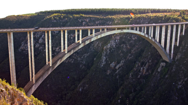 bloukrans bridge bungee  / natures valley sa / shot-2: person jumps - wide static shot with lens flare - south africa stock videos & royalty-free footage
