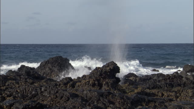Blowhole sprays seawater on rocky shore, Ascension Island