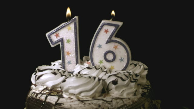 vidéos et rushes de cu slo mo blowing candle of number 16 on top of birthday cake / burbank, california, usa - gâteau d'anniversaire