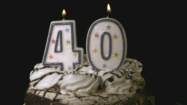 CU SLO MO Blowing candle of number 40 on top of birthday cake / Burbank, California, USA