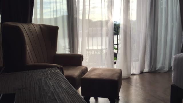 肘掛け椅子とカーテンを吹いています。 - 椅子点の映像素材/bロール
