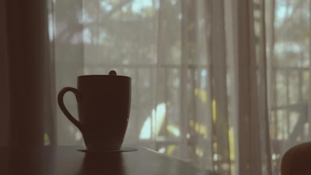 vídeos de stock, filmes e b-roll de cortina de sopro com um copo de café - poltrona