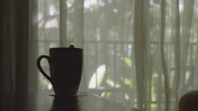 blowing curtain with a coffee cup - zoom out stock videos & royalty-free footage