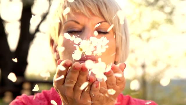 hd-super langsam mo: blasen blütenblättern in die kamera. - erwachsener über 30 stock-videos und b-roll-filmmaterial