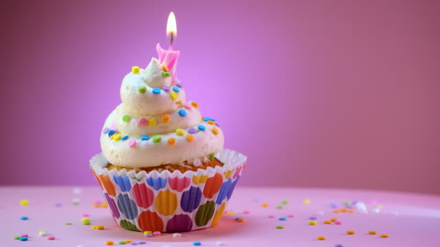 blowing out the candles of birthday decorated cupcake with sprinkles - single object stock videos & royalty-free footage
