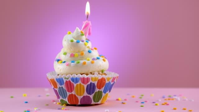 stockvideo's en b-roll-footage met het uitblazen van de kaarsen van verjaardag verfraaide cupcake met hagelslag - glijdend schot - enkel object