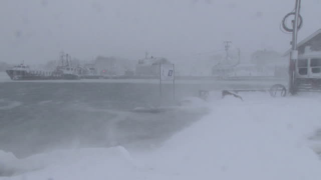 blowing snow hovers over an icy inlet during a new england blizzard. - coastal feature stock videos & royalty-free footage