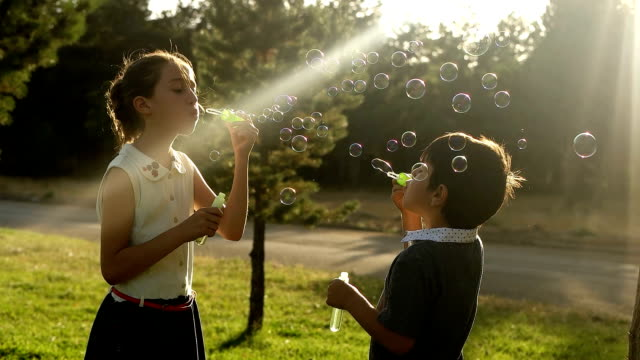 slow-mot blowing the bubbles with my friends - innocence stock videos & royalty-free footage