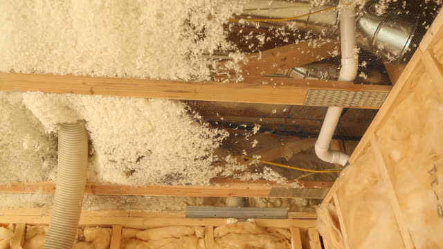 blown insulation installing between house floor joists - insulator stock videos & royalty-free footage