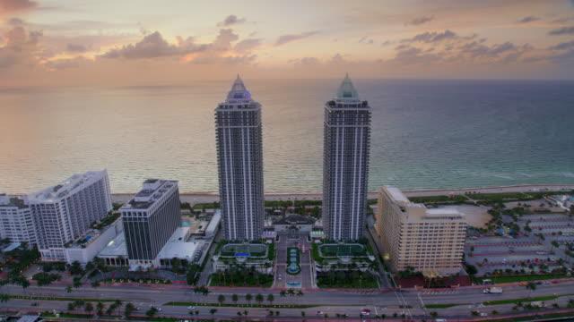vidéos et rushes de aerial blue and green diamond condominiums in miami beach, fl at dawn - miami
