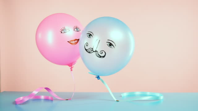 blue and pink helium balloons with faces