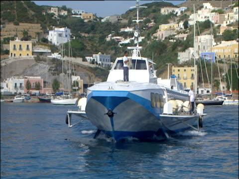 vídeos de stock e filmes b-roll de blue and white hydrofoil cruises towards camera pretty pastel coloured buildings on hills around harbour italy - embarcação comercial